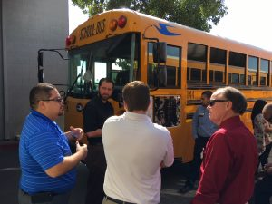 Image of parts and service employees at A-Z Bus Sales discussing Child Safety Alert System on a school bus